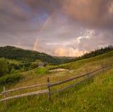 山的用花装饰的草甸在多云天空背景  库存照片