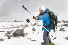 山的背包徒步旅行者假装射击在棍子的例子的箭头北欧走的 图库摄影