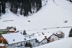 山的脚的积雪的山村在冬天下午,滑雪胜地Isch的 免版税图库摄影