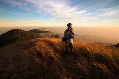 山的远足者在日落 免版税库存照片