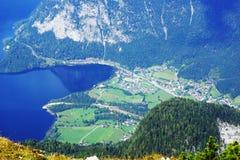 从山的顶端一个激动人心的景色向山村和一个深蓝色湖 免版税库存照片