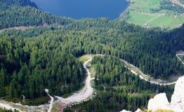 从山的顶端一个激动人心的景色向山村和一个深蓝色湖 图库摄影