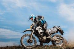 山的骑自行车的人从泥和石头下面后轮  库存图片