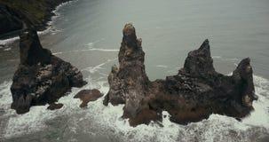 山的鸟瞰图在冰岛旋转有海鸥巢的脚趾对此 在峭壁附近的直升机飞行在黑海滩 股票视频