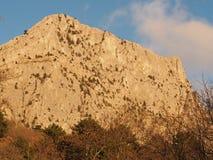 山石灰石小山,点燃由与下面海鸥的落日 免版税库存照片