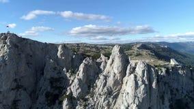 山空中览绳空中全景,在蓝色,多云天空背景的绿色树上 射击 迷人的峭壁 股票视频