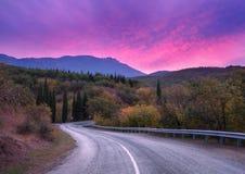 山穿过有剧烈的五颜六色的天空和红色云彩的森林的弯曲道路在黄昏在夏天 库存图片