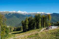 山绿色倾斜与多雪的山峰和电车的 免版税图库摄影