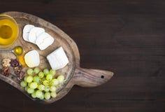 山羊与新鲜的greapes、核桃和蜂蜜的咸味干乳酪乳酪在铁锈 库存照片