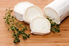山羊乳干酪用在一个木切板的麝香草 库存图片