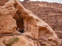 山羊休息在沙漠山的一个壁架下 库存照片