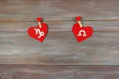 山羊座和标度 黄道十二宫和心脏 木后面 免版税图库摄影