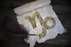 山羊座黄道十二宫在葡萄酒纸的与在书桌上的老笔 免版税库存照片