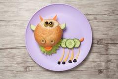 山羊由面包、乳酪和菜做成在板材和书桌 免版税库存图片