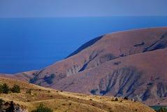 山美丽如画的倾斜没有植被的与站立在与蓝色海的一个倾斜边缘的人 库存照片