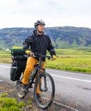 山背景的愉快的骑自行车的人在冰岛 库存图片