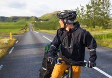 山背景的愉快的骑自行车的人在冰岛 免版税库存照片