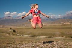 山背景的跳跃的女孩  免版税库存照片