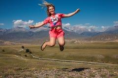 山背景的跳跃的女孩  免版税图库摄影