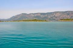 山背景的马尔马里斯港海滩美丽的蓝色海 免版税库存照片