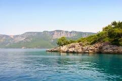 山背景的马尔马里斯港海滩美丽的蓝色海 库存照片