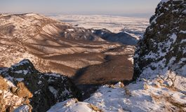 山脉在冬天,太阳的最后光芒 免版税库存图片