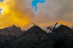 山脉雪锐化在橙色日落云彩下 图库摄影