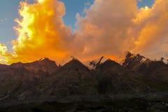 山脉雪锐化在橙色日落云彩下 库存照片