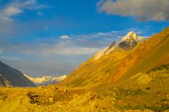 山脉雪锐化在橙色日落光下 免版税库存照片