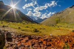 山脉风景与阳光、蓝天与云彩和一个小水道照亮的绿色山谷的有红色bac的 免版税库存图片
