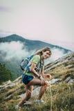 山腰的美丽的微笑的女孩 在背景云彩 库存照片