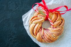 山莓果酱漩涡与红色丝带的奶油蛋卷花圈在黑st 免版税库存照片