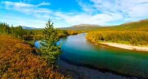 山蓝色清楚的河在五颜六色的秋天taiga森林里在与蓝天和白色云彩的一个晴天 图库摄影