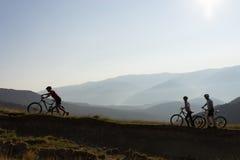 山行迹的三个骑自行车的人 免版税库存图片