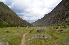 山谷和一串足迹在一个多云夏日 免版税库存图片