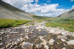 山谷蓝色多云天空的河在背景 自然夏天风景,俄罗斯,东部萨彦岭 图库摄影