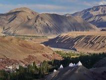 山谷高喜马拉雅山:在小山的前景是白色佛教stupas,在舒展桃红色和棕色山土坎后 库存图片