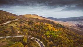 山路和秋天树在关岛峡谷'Guamka'在北高加索上,俄罗斯 黄色,红色和绿色自然,高梆的看法 免版税库存照片