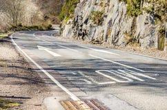 绕山路和警报信号在柏油碎石地面 库存照片