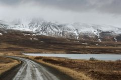 山路,很远多雪的山 免版税库存照片