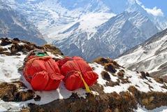 山远征的两个巨大的红色背包在雪 搬运工登山设备 库存照片