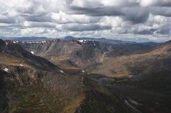 山雪排列和在多云幽暗黑暗天空背景的剧烈的谷  图库摄影