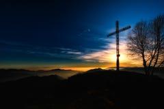 山顶十字架在日落的一座山 库存照片