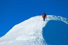 山顶的孤立男性爬山者 库存照片