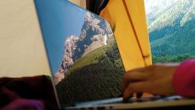 山风景在膝上型计算机屏幕被反射 妇女在旅游帐篷特写镜头使用一台计算机 股票录像