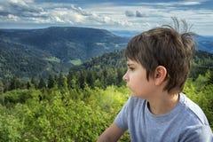 山风景背景的男小学生  免版税库存图片