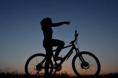 山骑自行车的人女孩剪影 库存照片