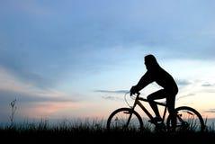 山骑自行车的人女孩剪影 图库摄影