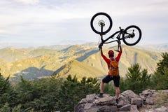 山骑自行车的人成功,看山景 免版税库存照片