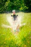 山骑自行车的人骑马通过一个大水坑 免版税库存照片